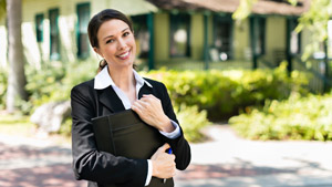 Smiling Realtor holding Padfolio in front of Home