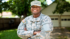Smiling military service member posing in front of his home