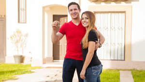 Young couple posing with house keys in front of new house
